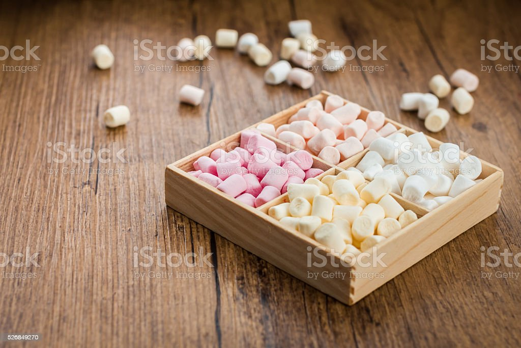 Box with marshmallows on the wooden background stock photo