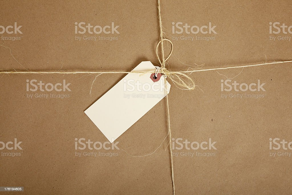 Box wrapped in brown paper with blank tag stock photo
