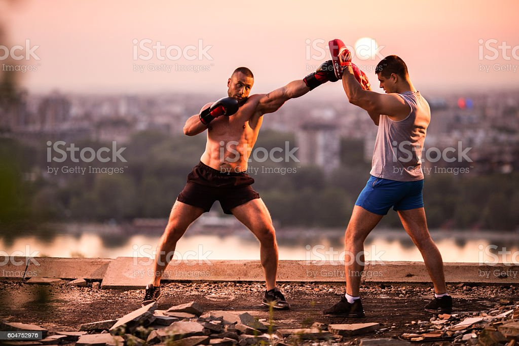 Boxer exercising at sunset with his personal sports trainer. stock photo