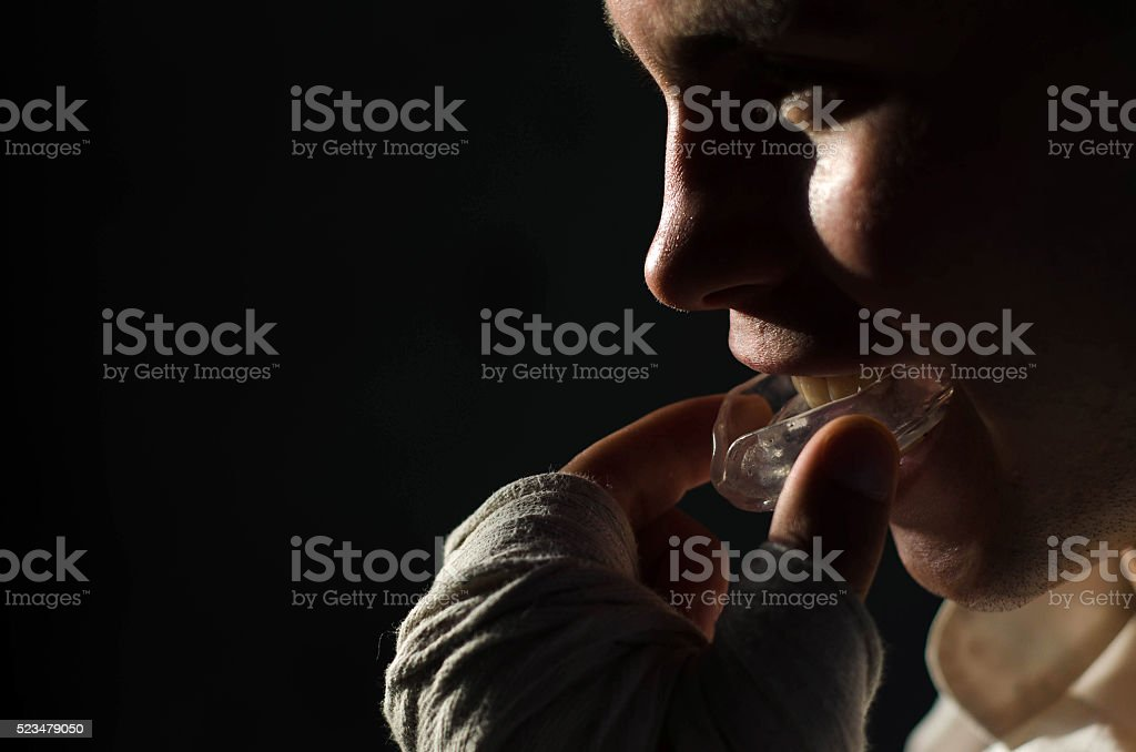 Boxer puts plastic teeth stock photo