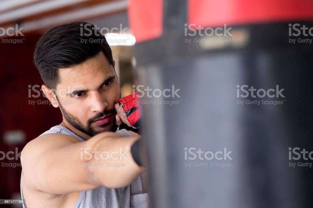 Boxer striking the punching bag at gym stock photo