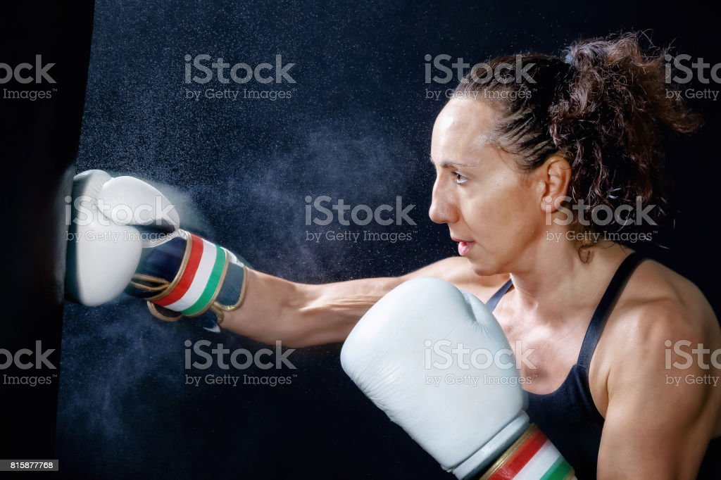 A boxer woman throws a punch in the sack. Splashes of water and sweat...