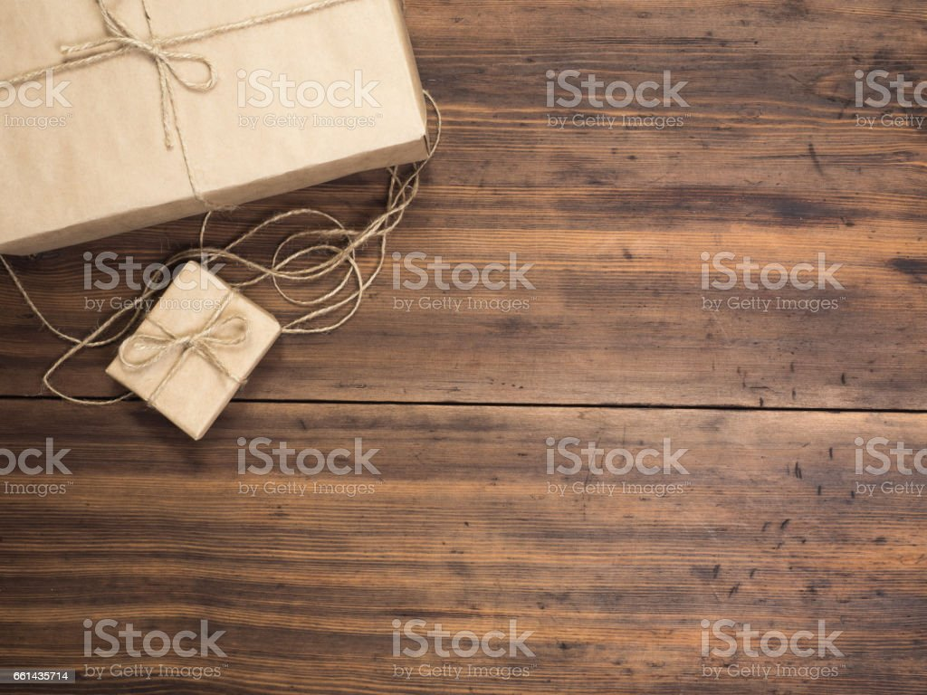 Boxes in craft paper, eco paper on the wooden table. Top view. Parcels or gifts tied with twine. Brown paper wrapped gift box with rope bow on a old rustic wood background stock photo
