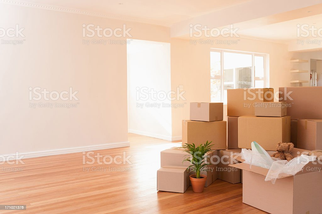 Boxes stacked on wooden floor of new house stock photo