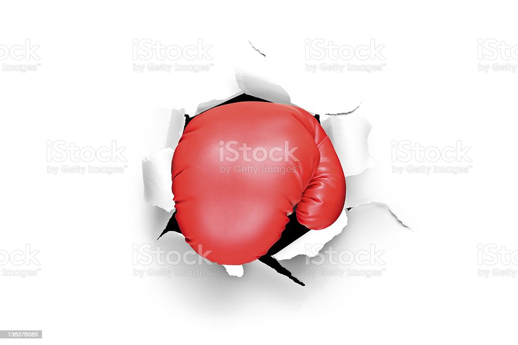 Boxing glove through a hole in paper stock photo