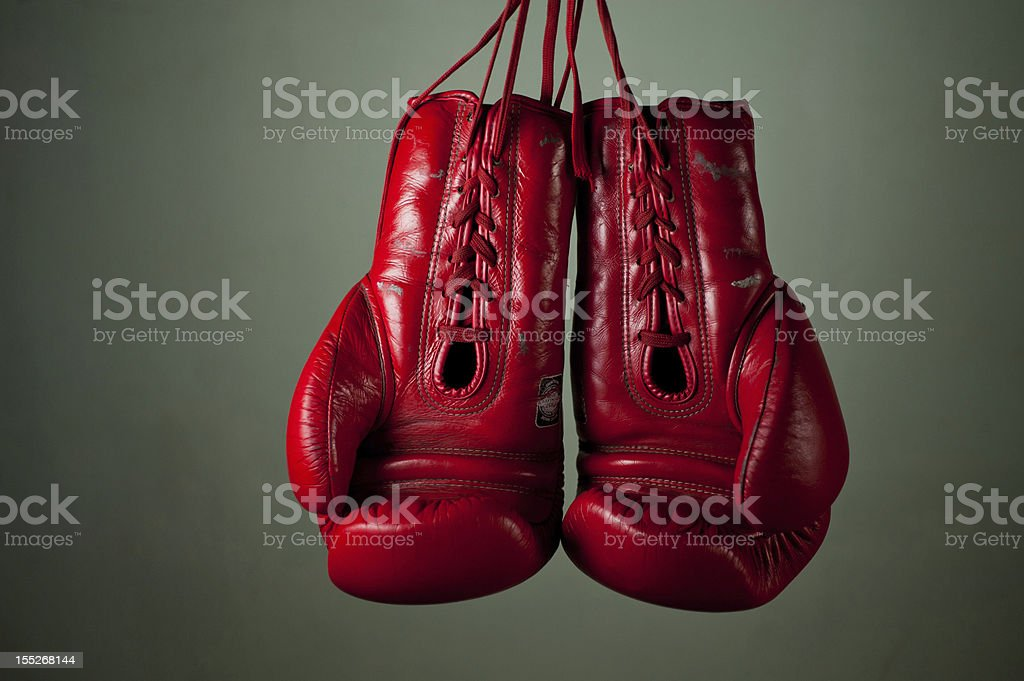 Boxing gloves hanging from laces on a grey background. stock photo