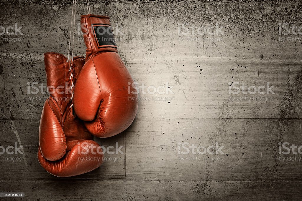 Boxing gloves hanging on concrete wall royalty-free stock photo