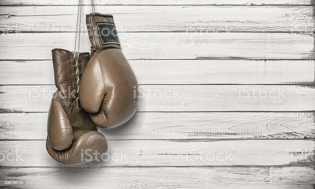 Boxing gloves hanging on wooden wall stock photo