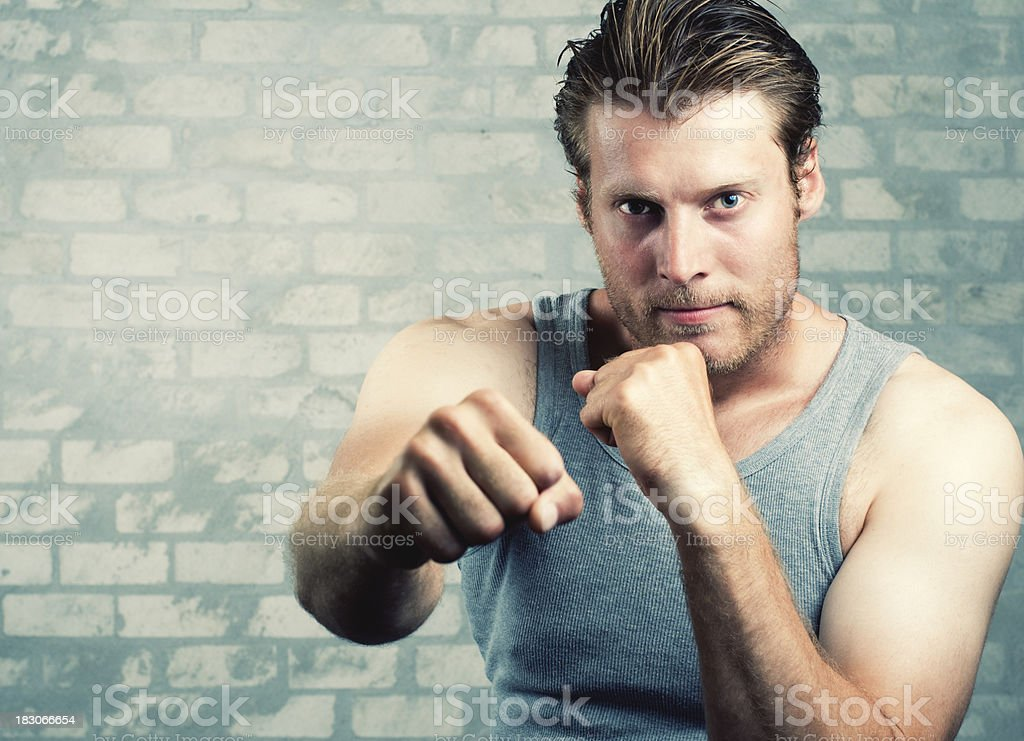 Boxing guy throws a punch at the camera. royalty-free stock photo