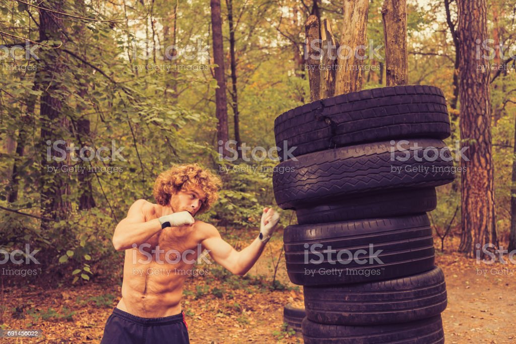 Boxing homemade pear, made from car tires. Fighter fulfills kick. stock photo
