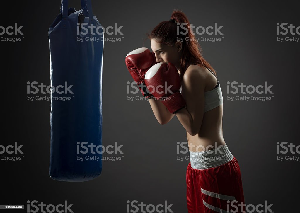 Boxing woman exercises with punching bag, on gray background stock photo