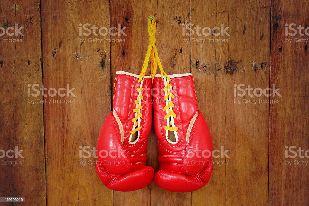 Boxing-glove hanging on wooden background stock photo