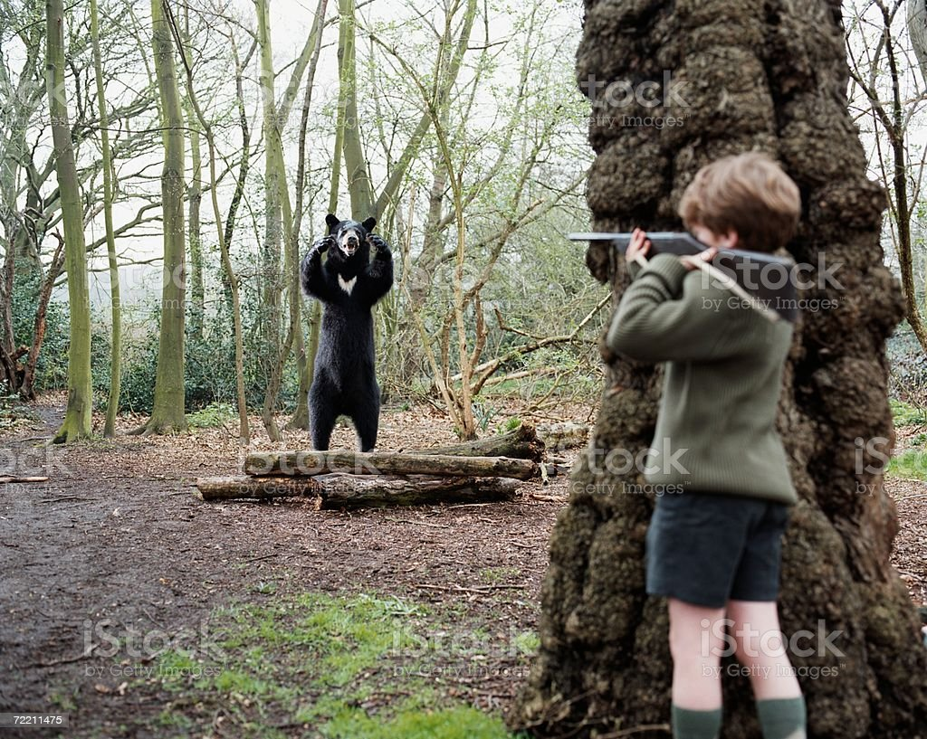 Boy about to shoot a bear stock photo
