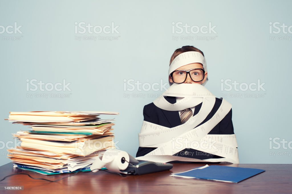 Boy Accountant Overworked and Covered in Paper stock photo