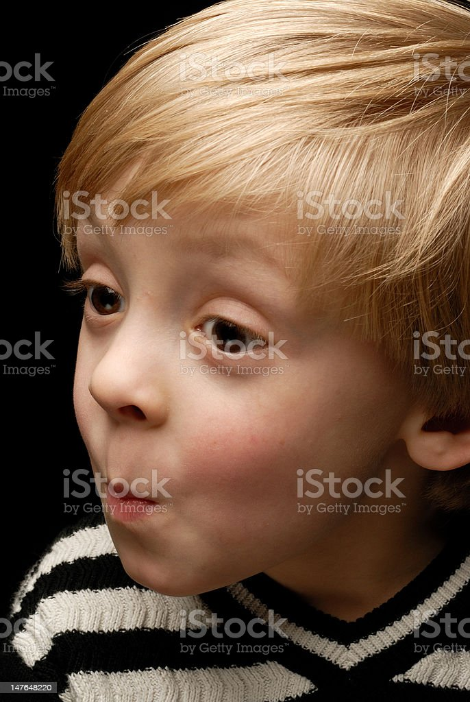 boy against black background making funny faces royalty-free stock photo