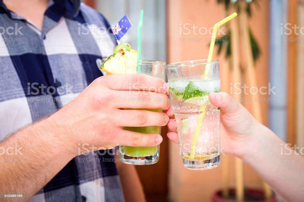 Boy and a young woman toasting with cocktails stock photo