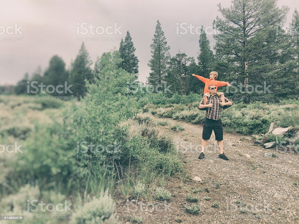 Boy and dad adventure together in the wilderness stock photo