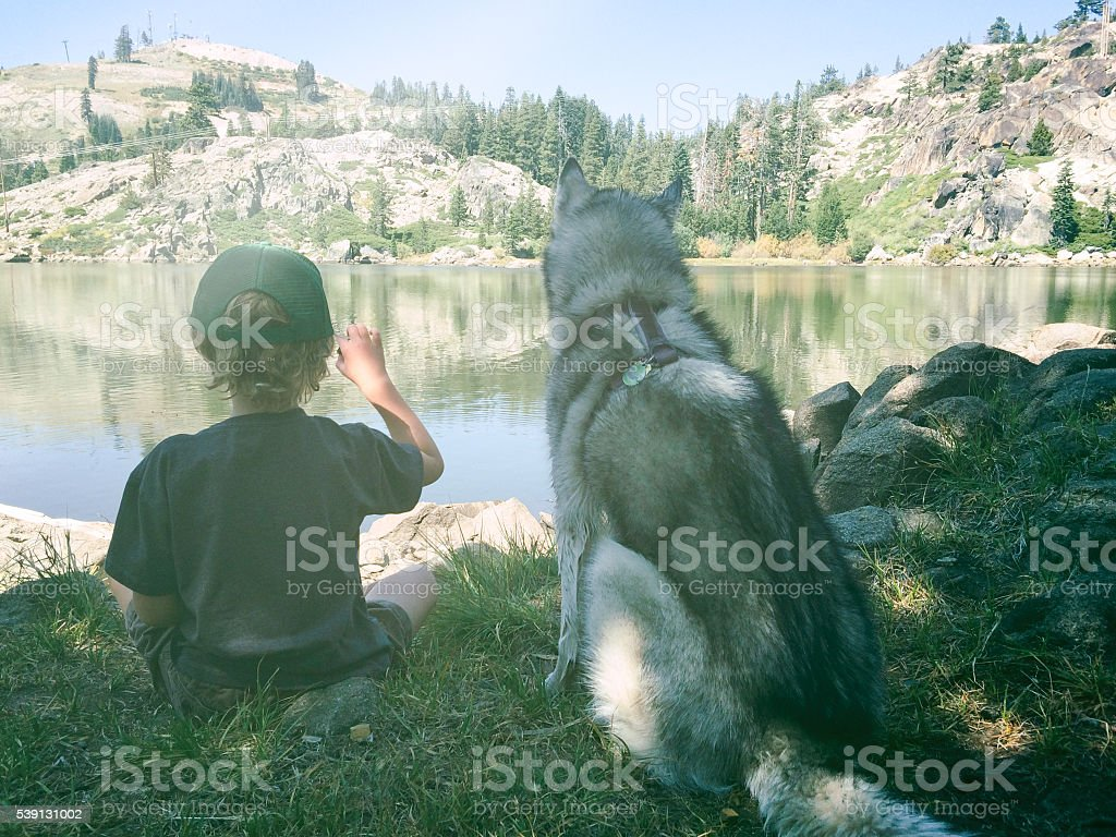 Boy and dog enjoy and afternoon on a mountain lake stock photo