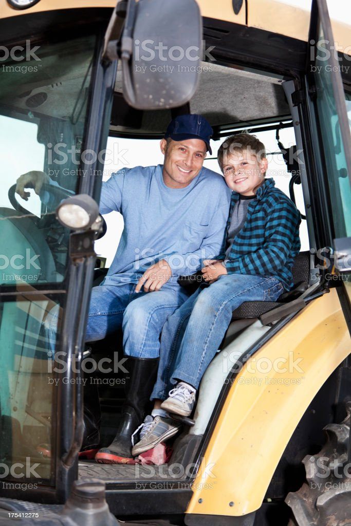 Boy and father on tractor stock photo
