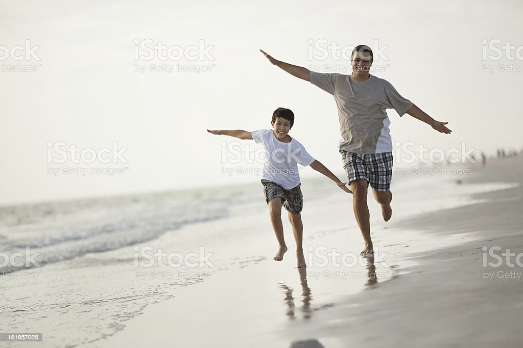 Boy And Father Running With Arms Outstretched Against Clear Sky royalty-free stock photo