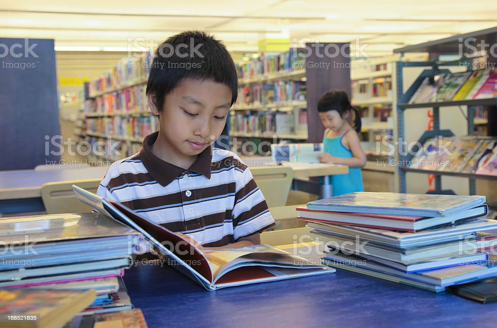 Boy and Girl Asian Kids Reading Books in A Library stock photo