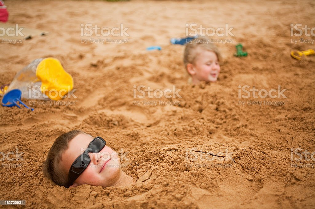 Boy and girl buried in sand. stock photo