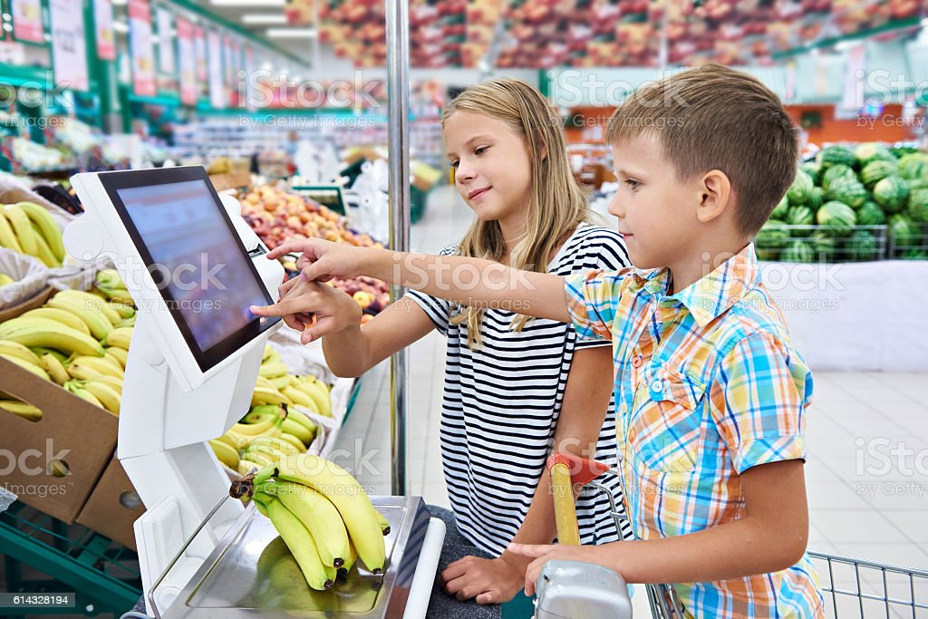 Boy and girl buying bananas in shop stock photo