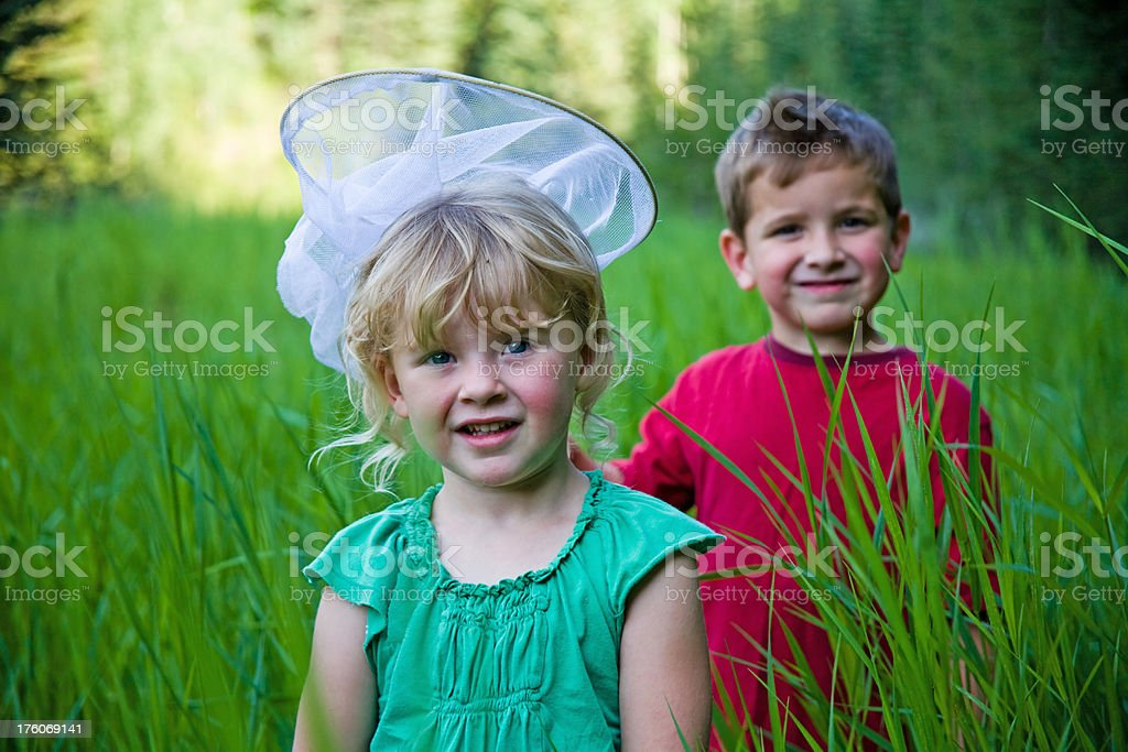 Boy and Girl Chasing Butterflies stock photo
