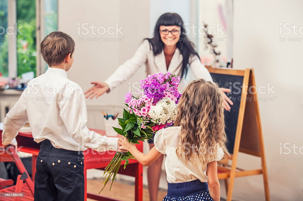 Boy and girl children give flowers as a school teacher stock photo