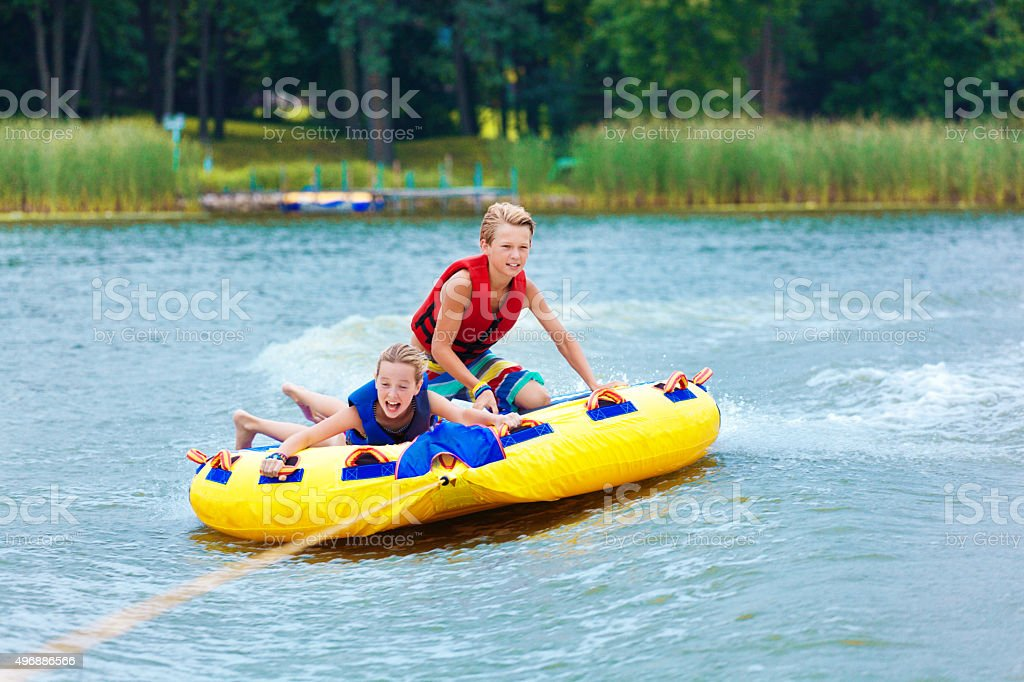 Boy and Girl Children Tubing on Minnesota Lake in Summer stock photo