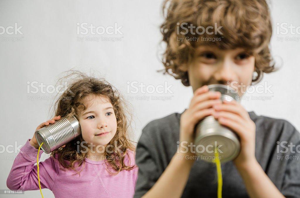 Boy and girl communicating through tin can phone stock photo