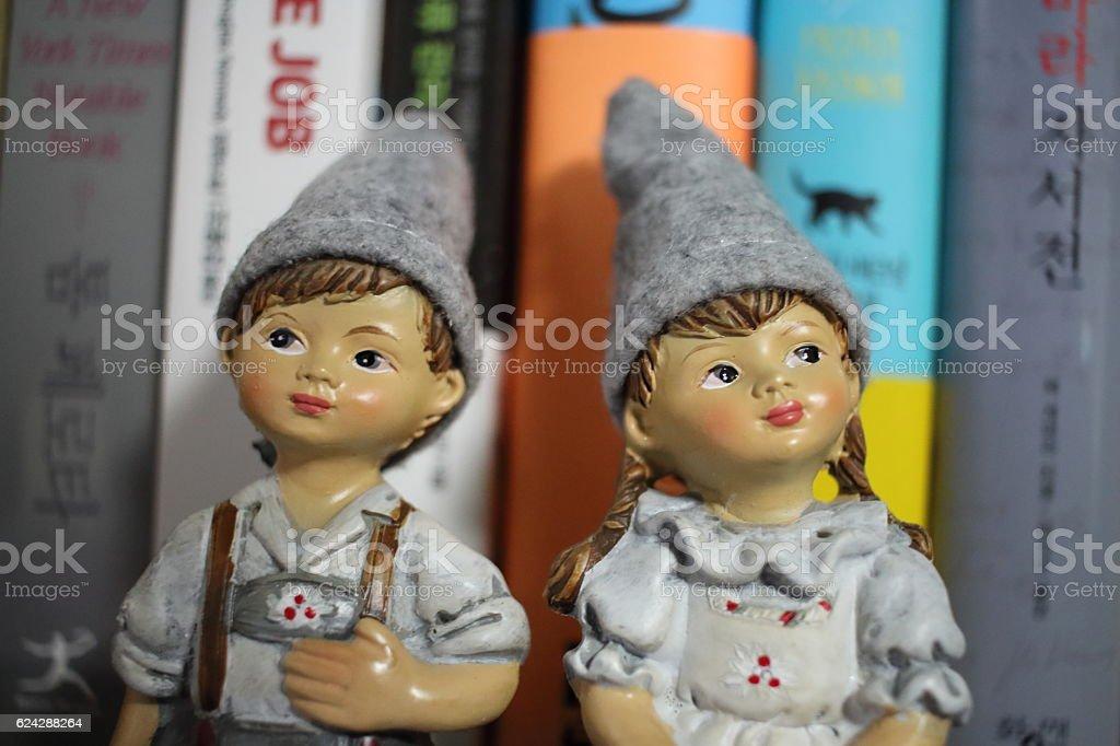 boy and girl dolls sitting on bookshelf stock photo