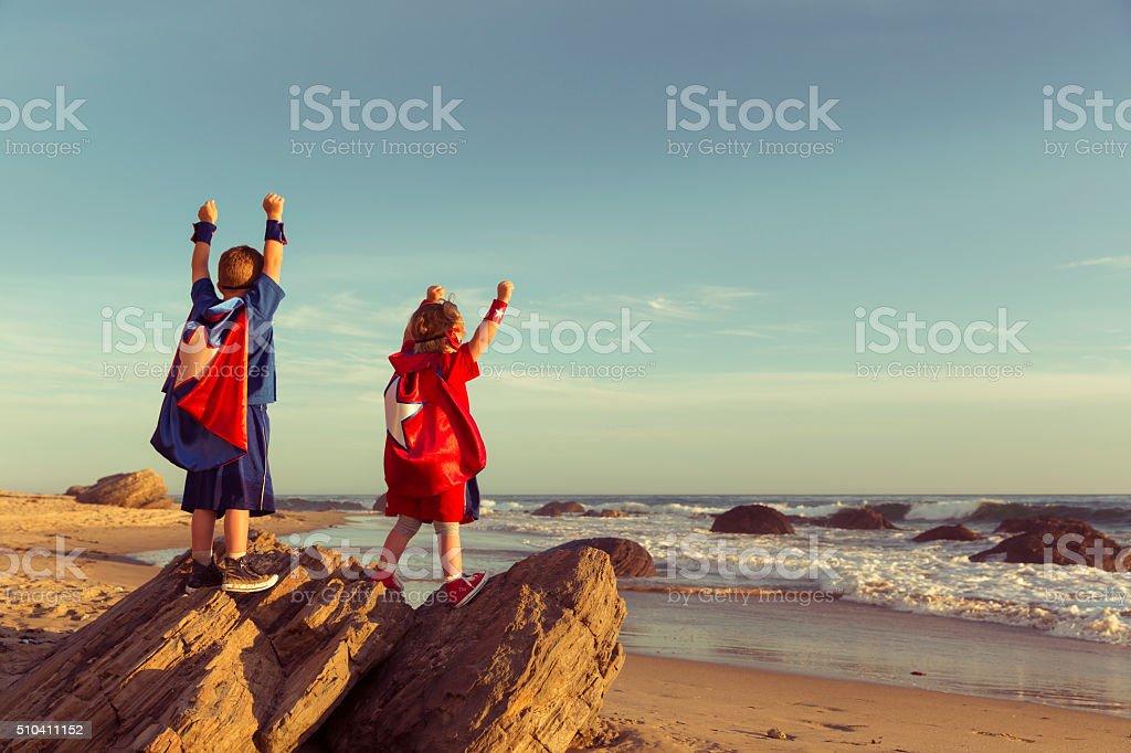 Boy and Girl dressed as Superheroes on California Beach stock photo