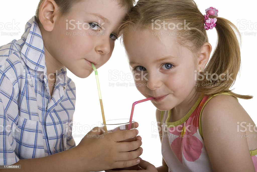 Boy and girl drinking with straws from the same glas royalty-free stock photo