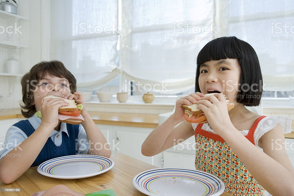Boy and girl eating sandwiches royalty-free stock photo