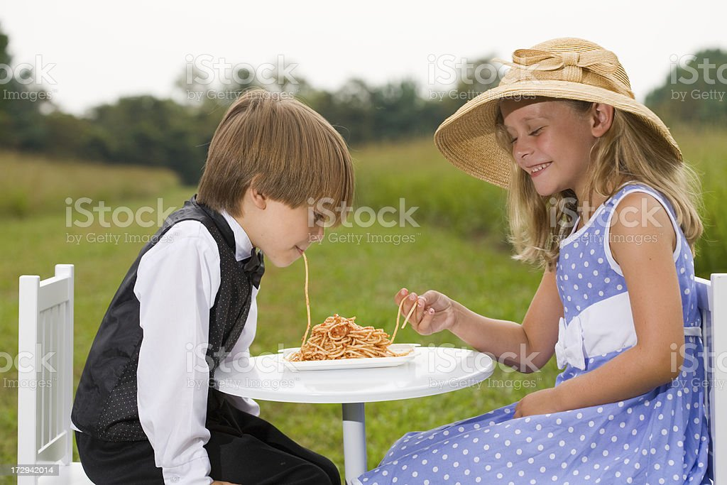 Boy and girl eating spaghetti at outdoor table royalty-free stock photo