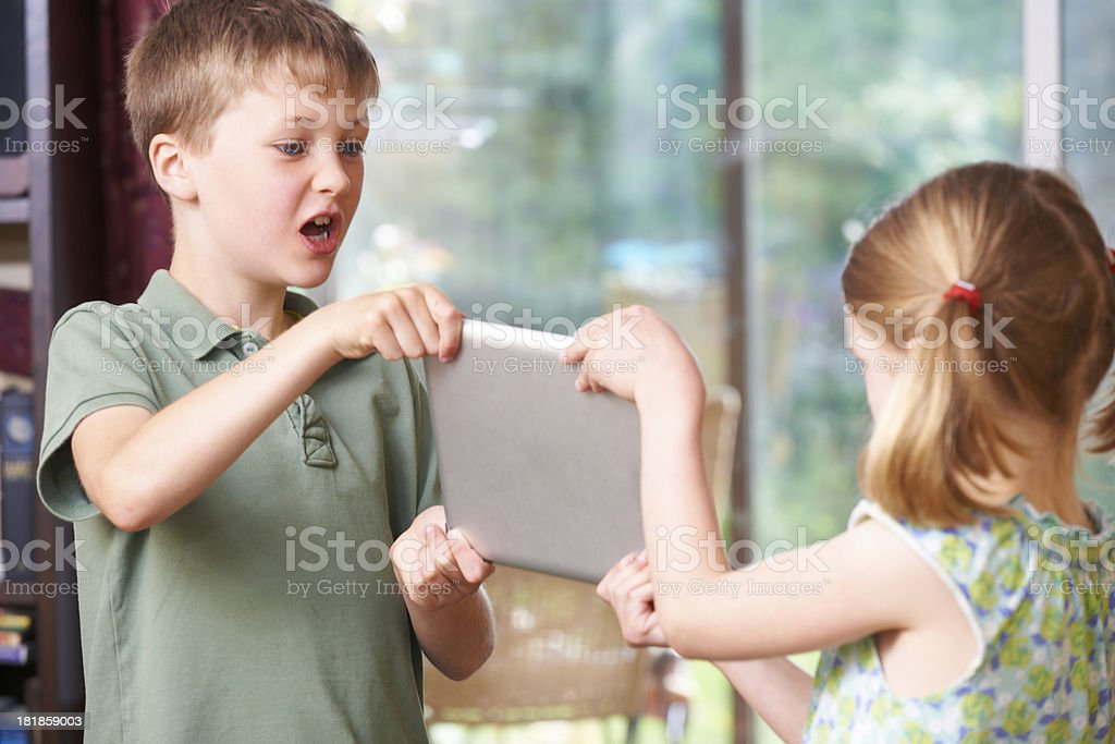 Boy And Girl Fighting Over Digital Tablet At Home stock photo