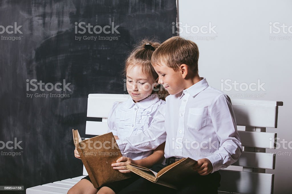 Boy and girl from primary school class on the bench stock photo
