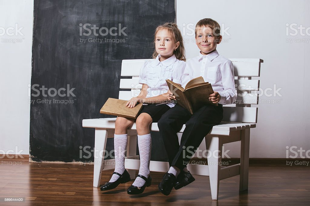 Boy and girl from primary school class read books stock photo