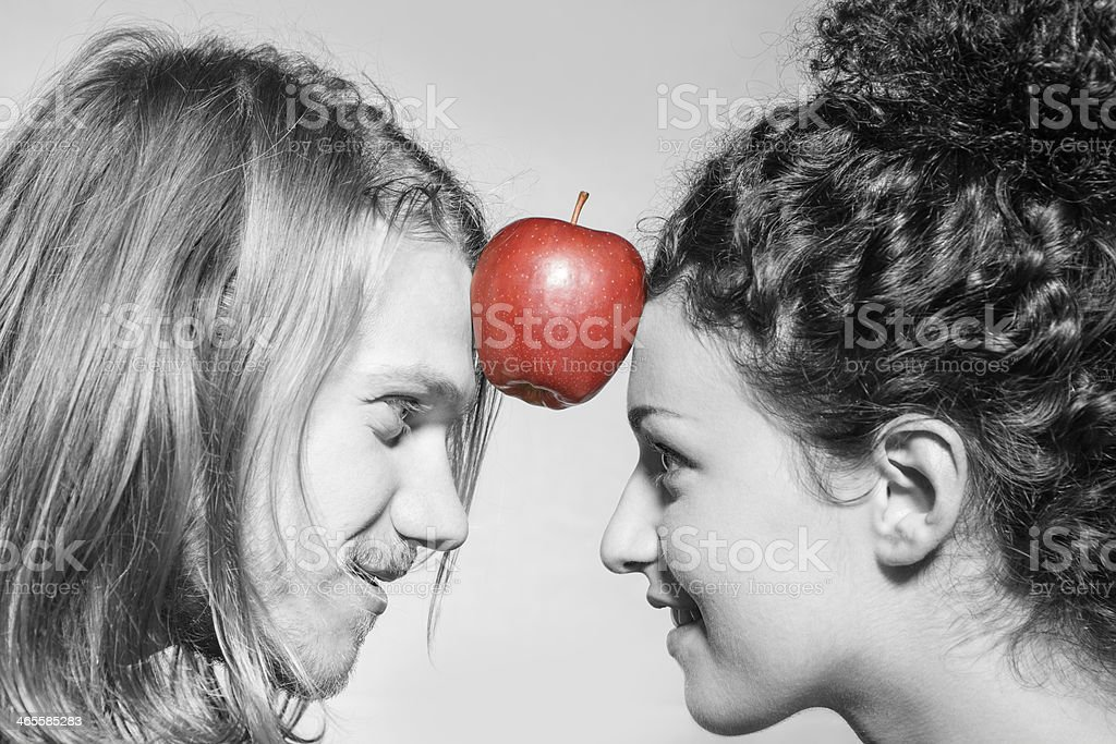 BW: Boy and girl holding an apple with forehead royalty-free stock photo