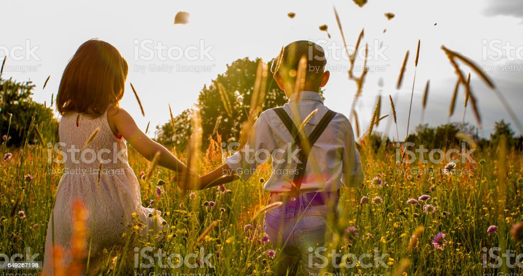 Boy and girl holding hands while walking on field stock photo