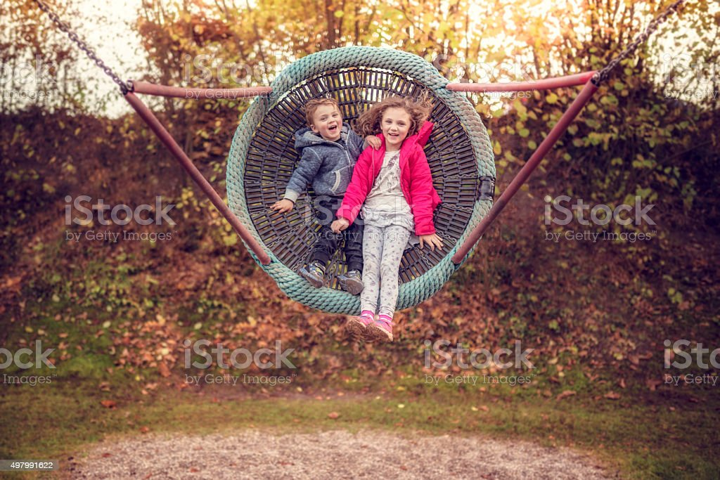 boy and girl in a big swing stock photo