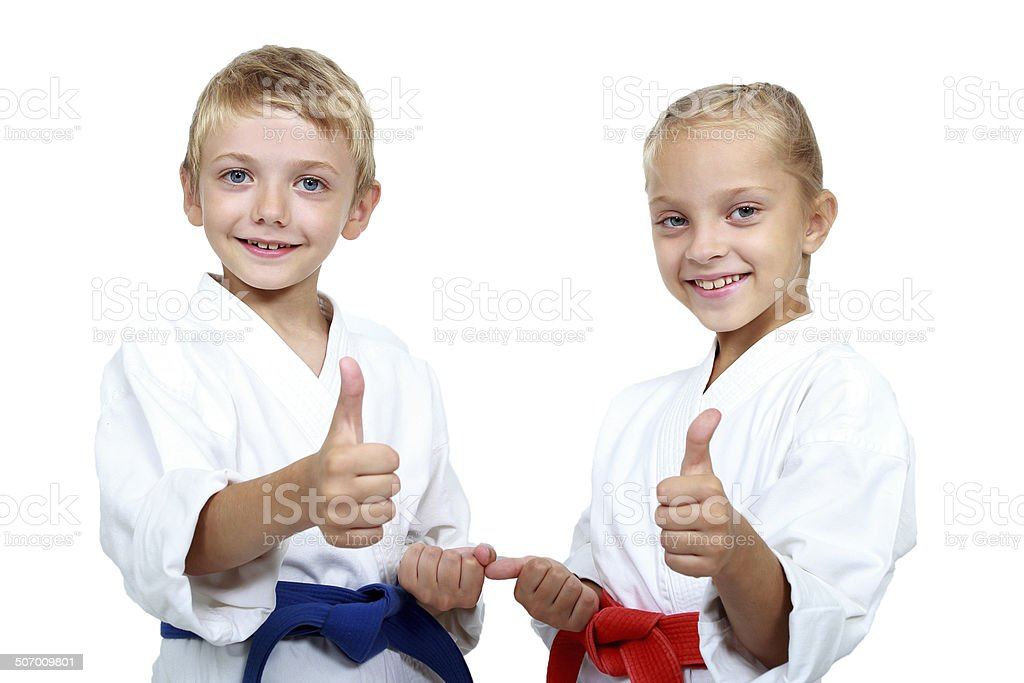 Boy and girl in karategi are showing thumb super stock photo
