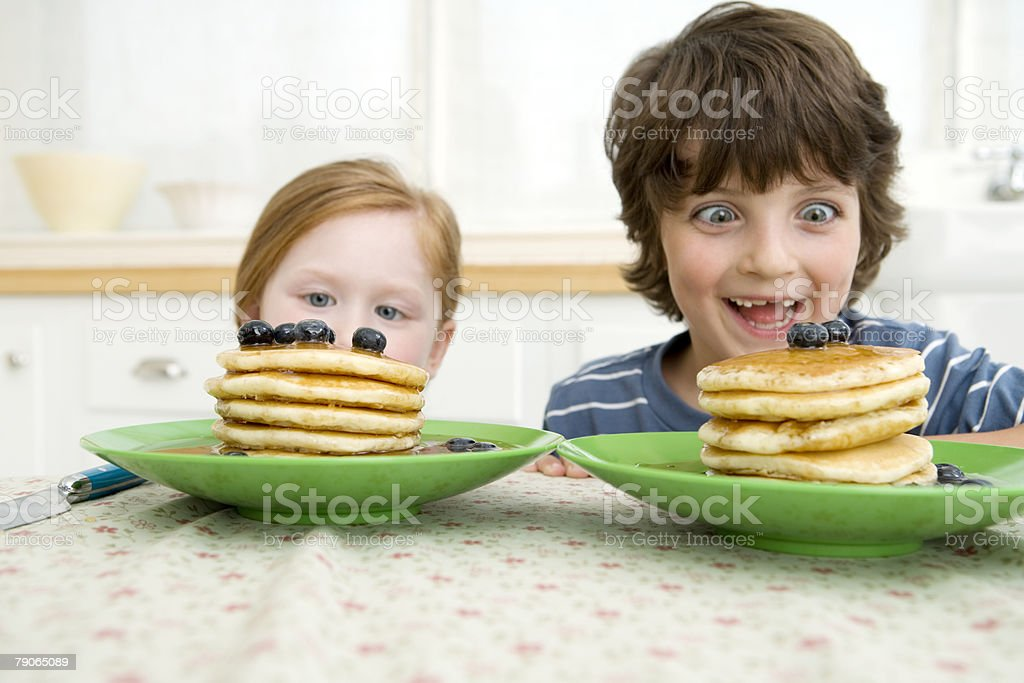 Boy and girl looking at pancakes stock photo