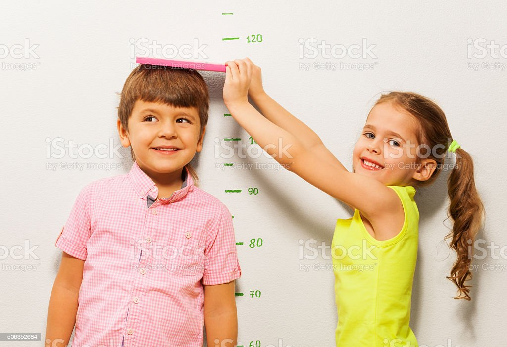 Boy and girl measure height by wall scale at home stock photo