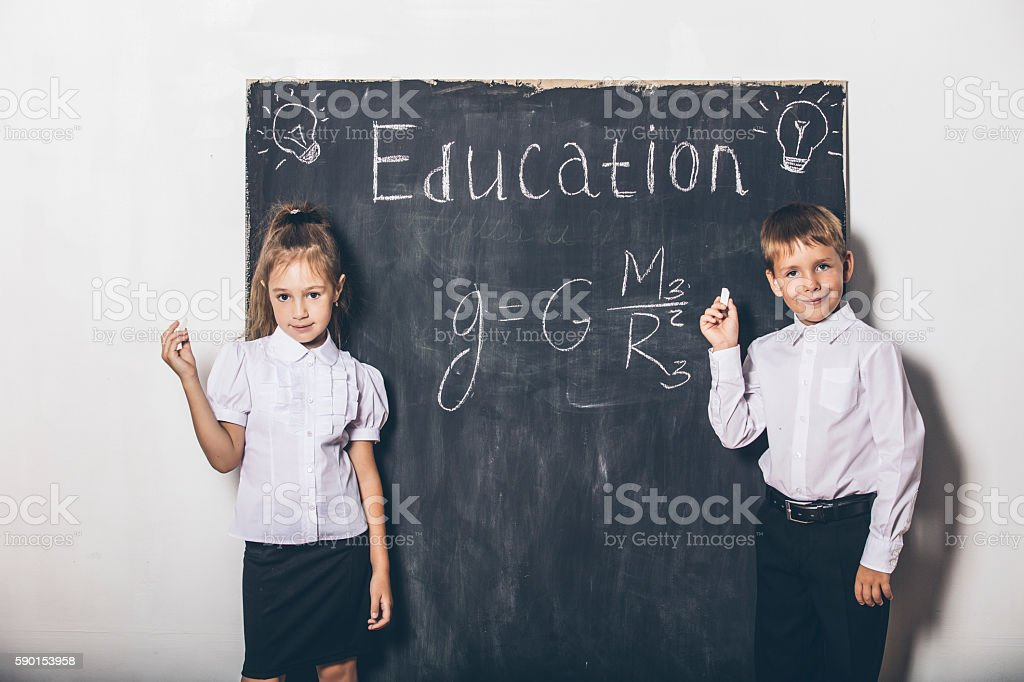 Boy and girl of elementary school in class background slate stock photo