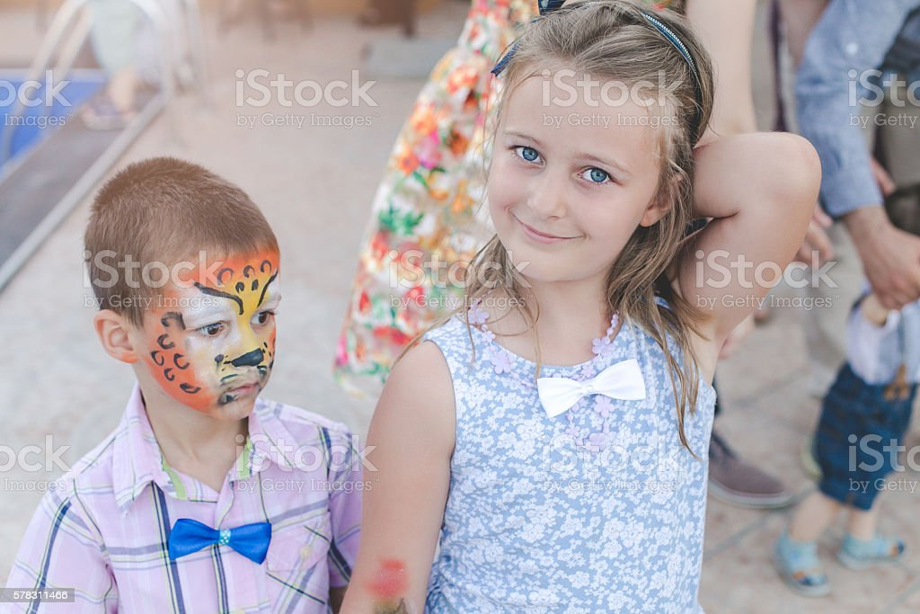 boy and girl on a party outside by the pool stock photo