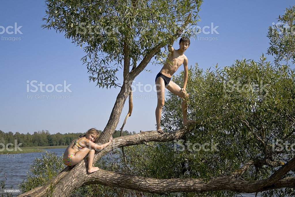 Boy and girl on a tree royalty-free stock photo