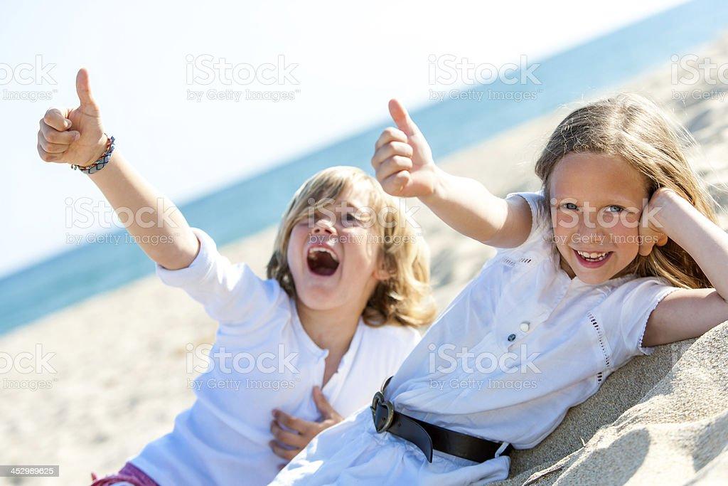 Garçon et fille sur la plage montrant thumbs up. photo libre de droits