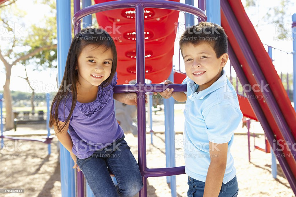 Boy And Girl On Climbing Frame In Park stock photo